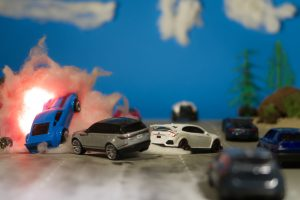 In this toy photo episode art, we see a busy highway shot, with eight cars, one of them in mid-explosion, with a fireball. In the background there are trees and clouds.